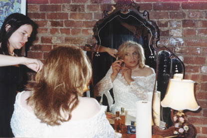Mirror, mirror on the wall. Gayle is the fairest of them all on her wedding day. Miss Melissa helps her get ready.