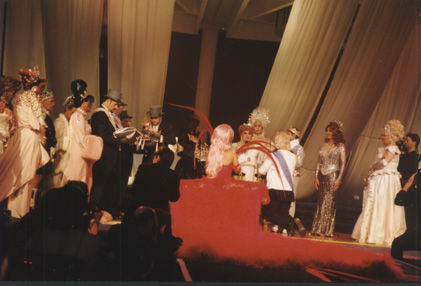 Imperial Coronation. A glowing pink feathered train extends behind incoming Empress XVI Lita Austin, the Schiaparelli Empress of Compassion and Couture as she kneels with Emperor XII Mathius Bloussant and the two await their crowns.